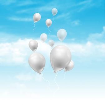 Balony unosi się w niebieskim niebie z puszystymi białymi chmurami