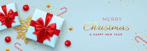 Baner bożonarodzeniowy realistyczne niebieskie pudełka na prezenty z czerwoną kokardą złote gwiazdki błyszczące złote płatki śniegu i laski cukierków