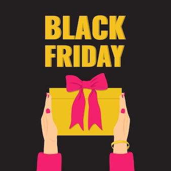 Baner na czarny piątek. ręce kobiety trzymającej żółty prezent z różową kokardką.