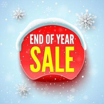 Baner sprzedaży na koniec roku z czerwoną okrągłą czapką śnieżną i płatkami śniegu