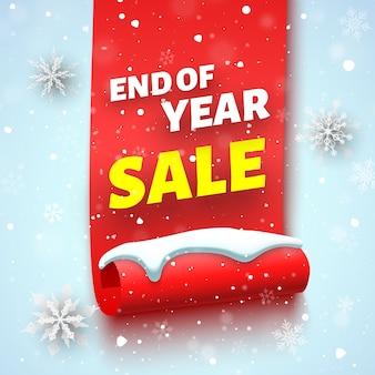 Baner sprzedaży na koniec roku z czerwoną wstążką, czapką śnieżną i płatkami śniegu.