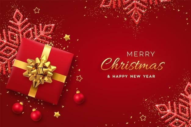 Baner świąteczny. realistyczne czerwone pudełko ze złotą kokardką, błyszczącym płatkiem śniegu