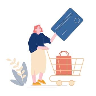 Bezkontaktowa koncepcja płatności. kobieta-klientka stoi w supermarkecie i przygotowuje kartę kredytową do bezgotówkowych płatności online. kobieta kupujący pchający wózek z towarem w sklepie. kreskówka