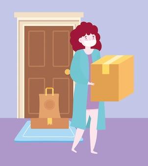 Bezpieczna dostawa w domu podczas koronawirusa covid-19, kobieta niosąca pudełko i zamówienie w drzwiach