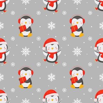 Bezszwowe tło boże narodzenie z słodkie pingwiny i płatki śniegu.