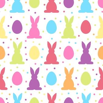 Bezszwowy wzór z kolorowymi wielkanocnymi jajkami i królikami
