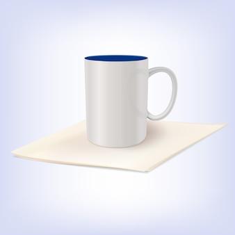 Biała ceramiczna filiżanka stoi na serwetce