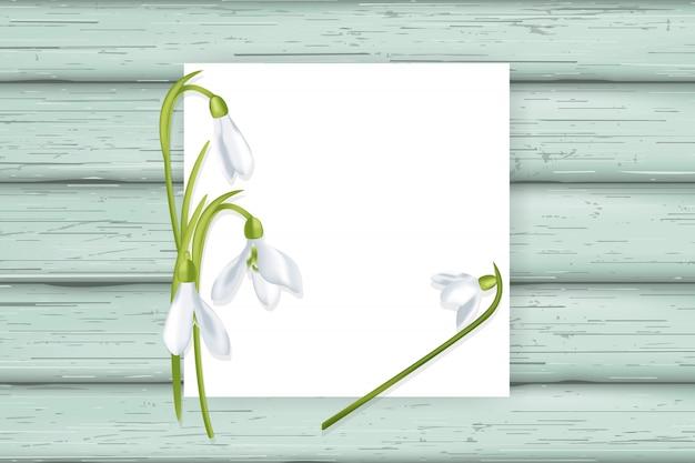 Biała kartka z przebiśniegami na drewnianych