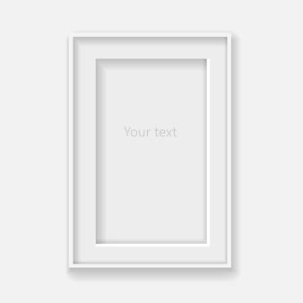 Biała ramka pionowa na szarej ścianie z cieniami.