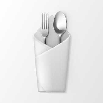 Biała serwetka składana koperta ze srebrnym widelcem i łyżką widok z góry na białym tle. ustawienie stołu