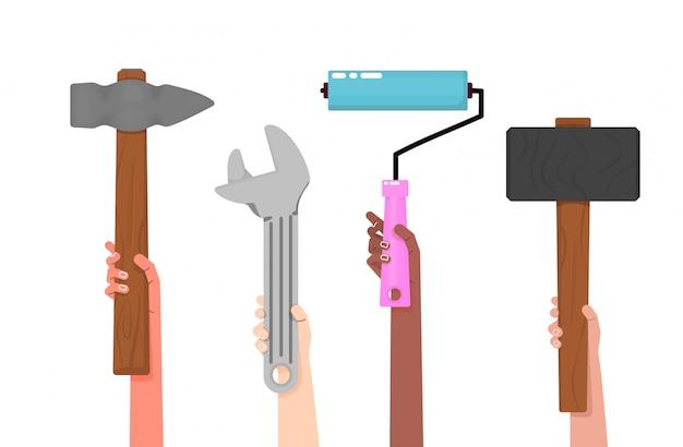 Białe i czarne ręce trzymają narzędzia