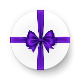 Białe okrągłe pudełko z błyszczącą fioletową fioletową satynową kokardką i wstążką