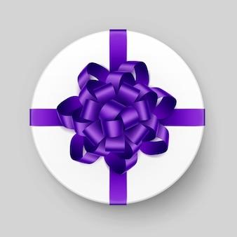 Białe okrągłe pudełko z błyszczącą fioletową kokardą i wstążką widok z góry z bliska na białym tle na tle