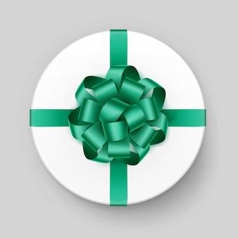 Białe okrągłe pudełko z błyszczącą zieloną szmaragdową kokardą i wstążką widok z góry z bliska na tle