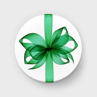 Białe okrągłe pudełko z przezroczystą zieloną szmaragdową kokardą i wstążką widok z góry z bliska na białym tle na tle