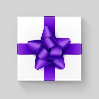 Białe pudełko prezentowe z kokardą z fioletowej fioletowej wstążki