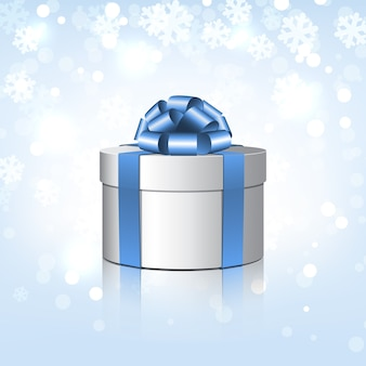 Białe pudełko upominkowe z niebieską kokardką. ilustracja na tle śniegu