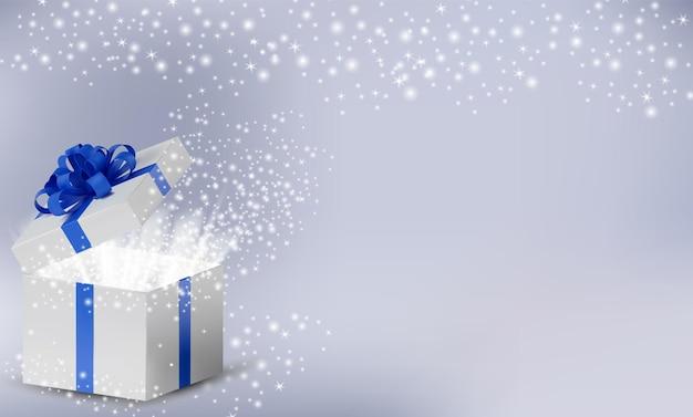 Białe pudełko z niebieską wstążką i kokardką na górze. otwarte pudełko świąteczne ze świecącymi brokatowymi błyskami i magicznym światłem w środku.