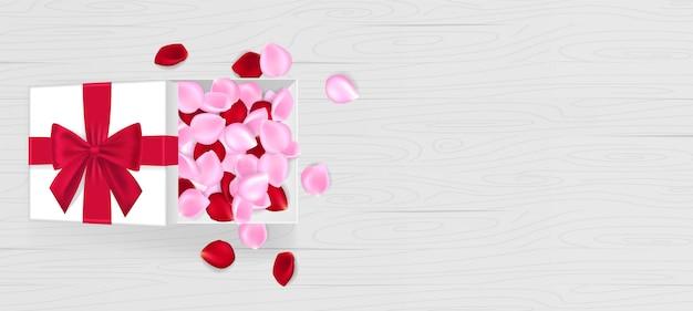 Białe pudełko z płatkami róży, kokardkami i wstążkami na czerwono. płatki róż