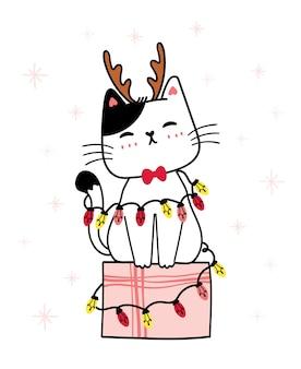 Biały kotek kot nosi renifera poroża siedzieć na pudełku z lekkim sznurkiem garland blub, życzenia bożonarodzeniowe, ilustracja kreskówka, nadruk dla dzieci, z płatkiem śniegu w tle
