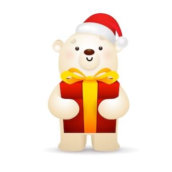 Biały niedźwiedź w santa hat gospodarstwa świąteczny prezent
