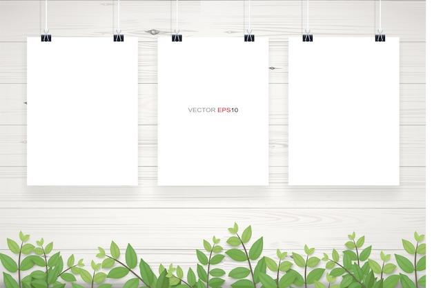 Biały papier plakat wiszący na białej drewnianej ścianie tekstura tło z zielonymi liśćmi ramki