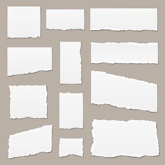 Biały podarty papier. podarte strzępy papieru. kawałki papieru na białym tle. zgrane paski papieru