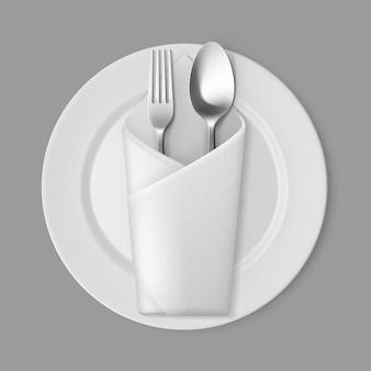Biały pusty okrągły talerz srebrny widelec łyżka koperta serwetka