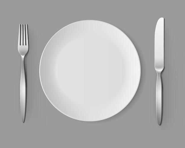 Biały pusty okrągły talerz z ustawieniem stołu nóż widelec