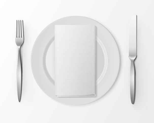 Biały pusty płaski okrągły talerz z srebrnym widelcem i nożem i białą serwetką składaną prostokątną na białym tle, widok z góry na białym.