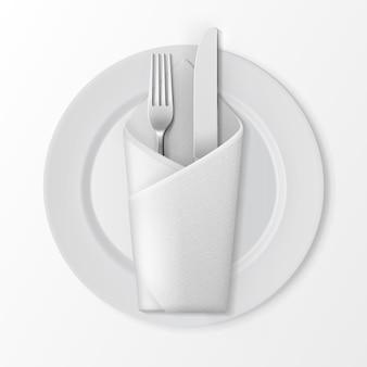 Biały pusty płaski okrągły talerz ze srebrnym widelcem i nożem i biały serwetka składana koperta widok z góry na białym tle. ustawienie stołu