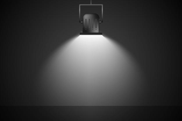 Biały reflektor jest oświetlony na ciemnej ścianie