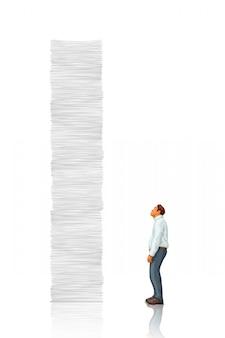 Biały wysoki stos papieru kontra człowiek
