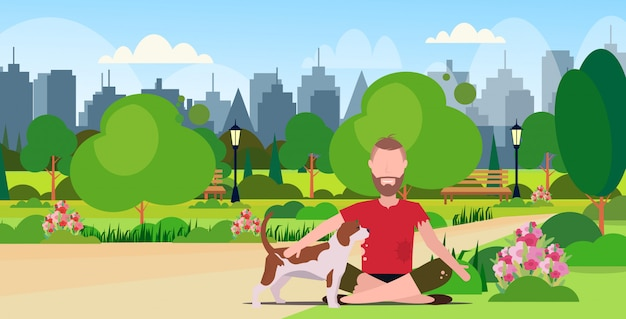 Biedny brodaty mężczyzna z psem siedzi w parku miejskim facet żebrak o pomoc bezdomny krajobraz pełnej długości