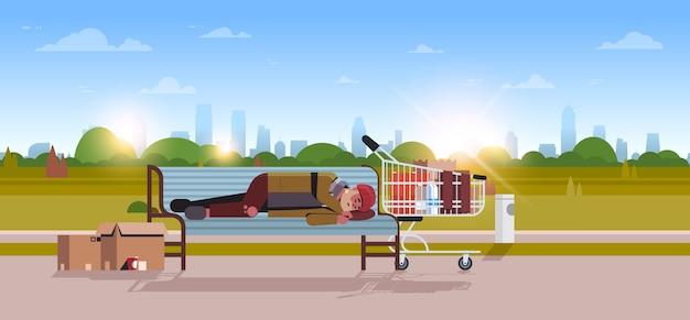 Biedny człowiek śpi na zewnątrz pijany żebrak leżący na drewnianej ławce bezdomny miasto park krajobraz wschód słońca