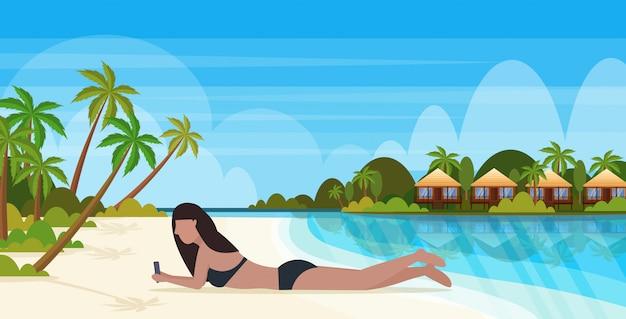 Bikini kobieta opalanie dziewczyna w stroju kąpielowym za pomocą smartfona komunikacji społecznej mediów wakacje wakacje koncepcja bunglow dom krajobraz tło pełnej długości poziomej