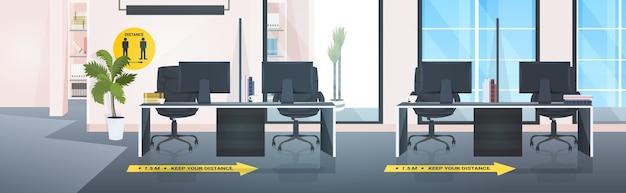 Biurka w miejscu pracy z oznakowaniem żółtych naklejek dystansujących społeczność środków ochrony przed epidemią koronawirusa