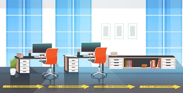 Biurka w miejscu pracy z tabliczkami informującymi o ochronie przed epidemią koronawirusa