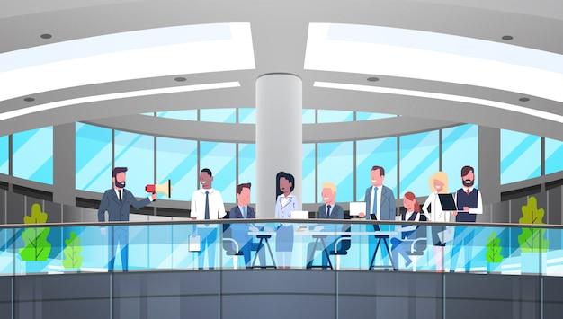 Biznes człowiek lider rozmowy w megafon podczas spotkania z zespołem przedsiębiorców w nowoczesnym biurze