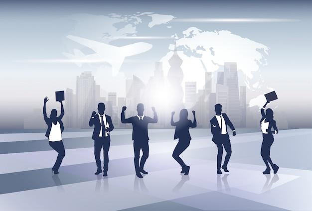 Biznes drużyna sylwetki biznesmenów grupa rozochocona szczęśliwa podnosząca ręka nad światowej mapy wycieczki lotem