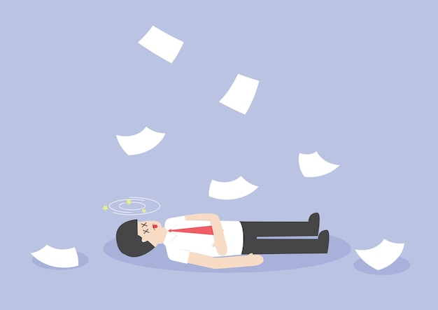 Biznesmen ciężko pracuje i nieprzytomny na podłodze