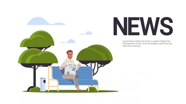 Biznesmen gospodarstwa gazeta czytanie codzienne wiadomości prasa środki masowego przekazu koncepcja mężczyzna siedzi na drewnianej ławce