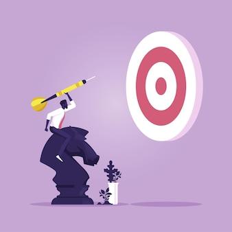 Biznesmen jedzie w szachy rycerza i trzyma strzałkę, aby osiągnąć cel cele osiągnięć ze strategią