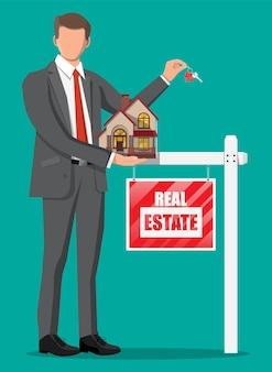 Biznesmen lub pośrednik w handlu nieruchomościami posiadający dom i klucz. drewniany afisz ze znakiem nieruchomości. kredyt hipoteczny, nieruchomości i inwestycje. kup sprzedaj lub wynajmij nieruchomość. płaska ilustracja wektorowa