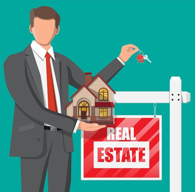 Biznesmen lub pośrednik w handlu nieruchomościami posiadający dom i klucz