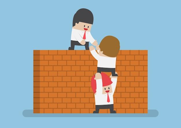 Biznesmen pomóc swojemu przyjacielowi przejść przez mur z cegły, koncepcja pracy zespołowej