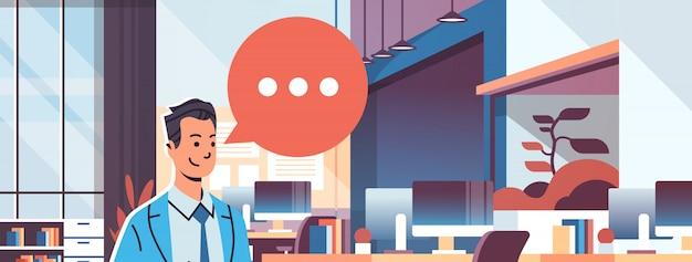 Biznesmen posiadania tabletu mowy czat bąbelek ikona transparent