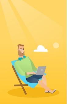 Biznesmen pracuje na laptopie na plaży.