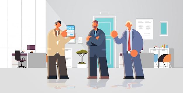 Biznesmen przedstawia pieniężnego diagrama statystyki dane raport na pastylka ekranie koledzy biznesmeni zespala się brainstorming nowożytnego biurowego wewnętrznego płaskiego pełnego długość horyzontalnego