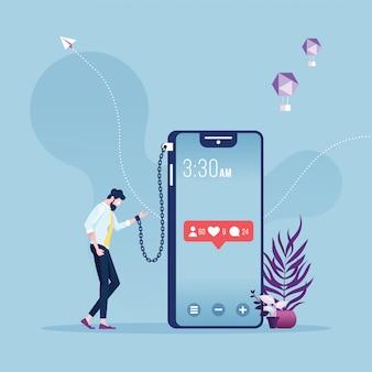 Biznesmen przykuty i przykuty do wielkiego smartfona - metafora uzależnienia od sieci społecznościowych